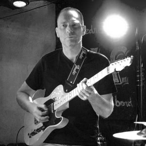 black and white photo of rob williams playing the guitar