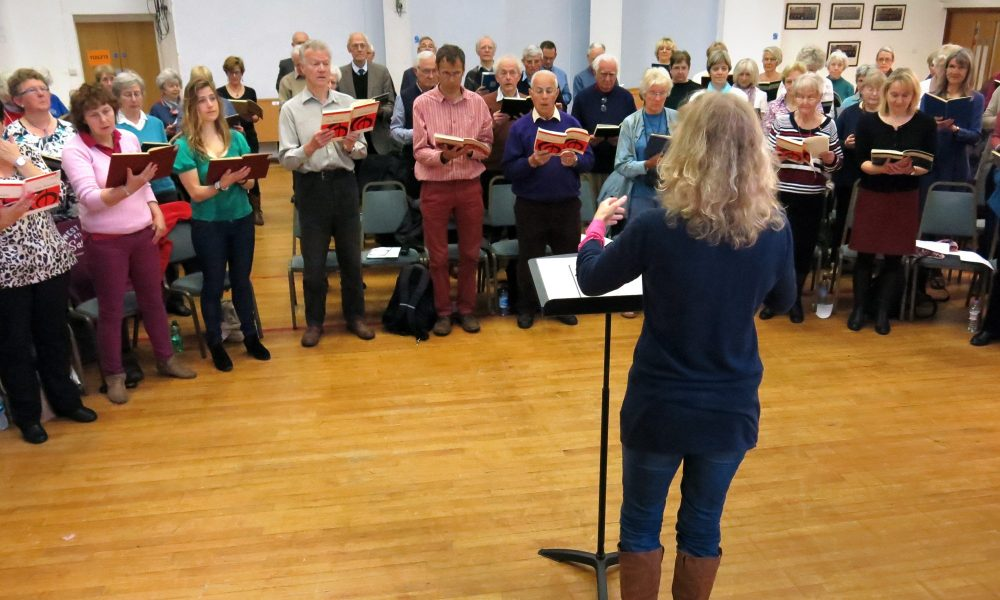 Catherine Hamilton singing and vocals teacher in rehearsal with a choir